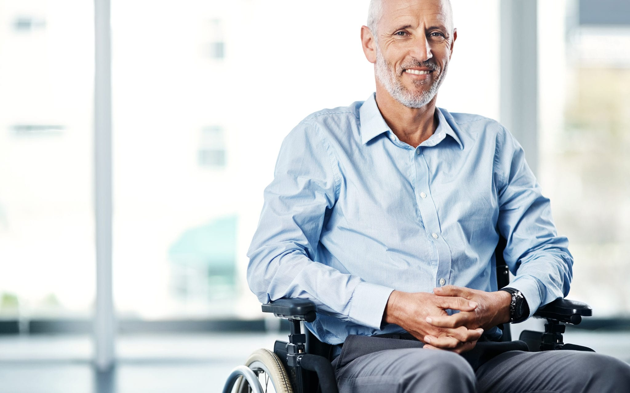 Older patient in wheelchair who may have social determinants of health to be addressed with patient engagement