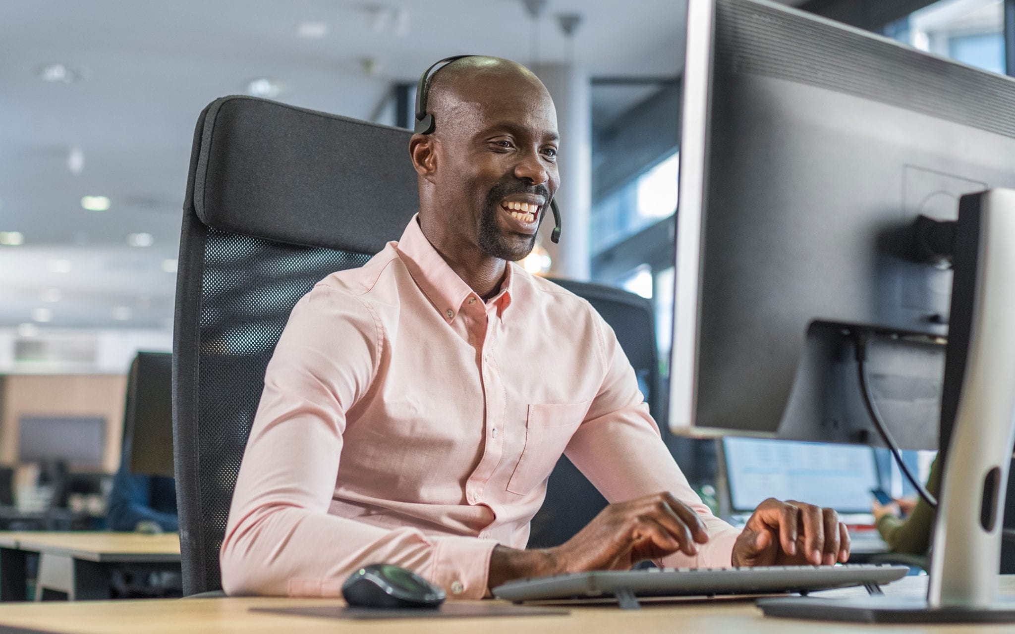 Smiling man working on appointment scheduling at computer and with headset