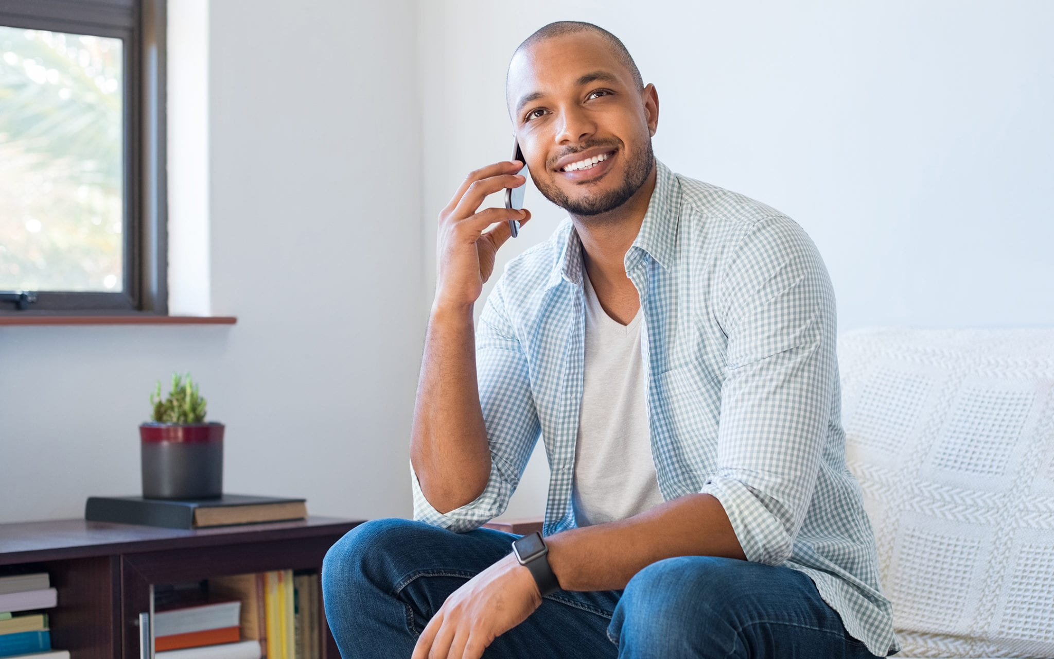 Young man smiling, using his mobile phone