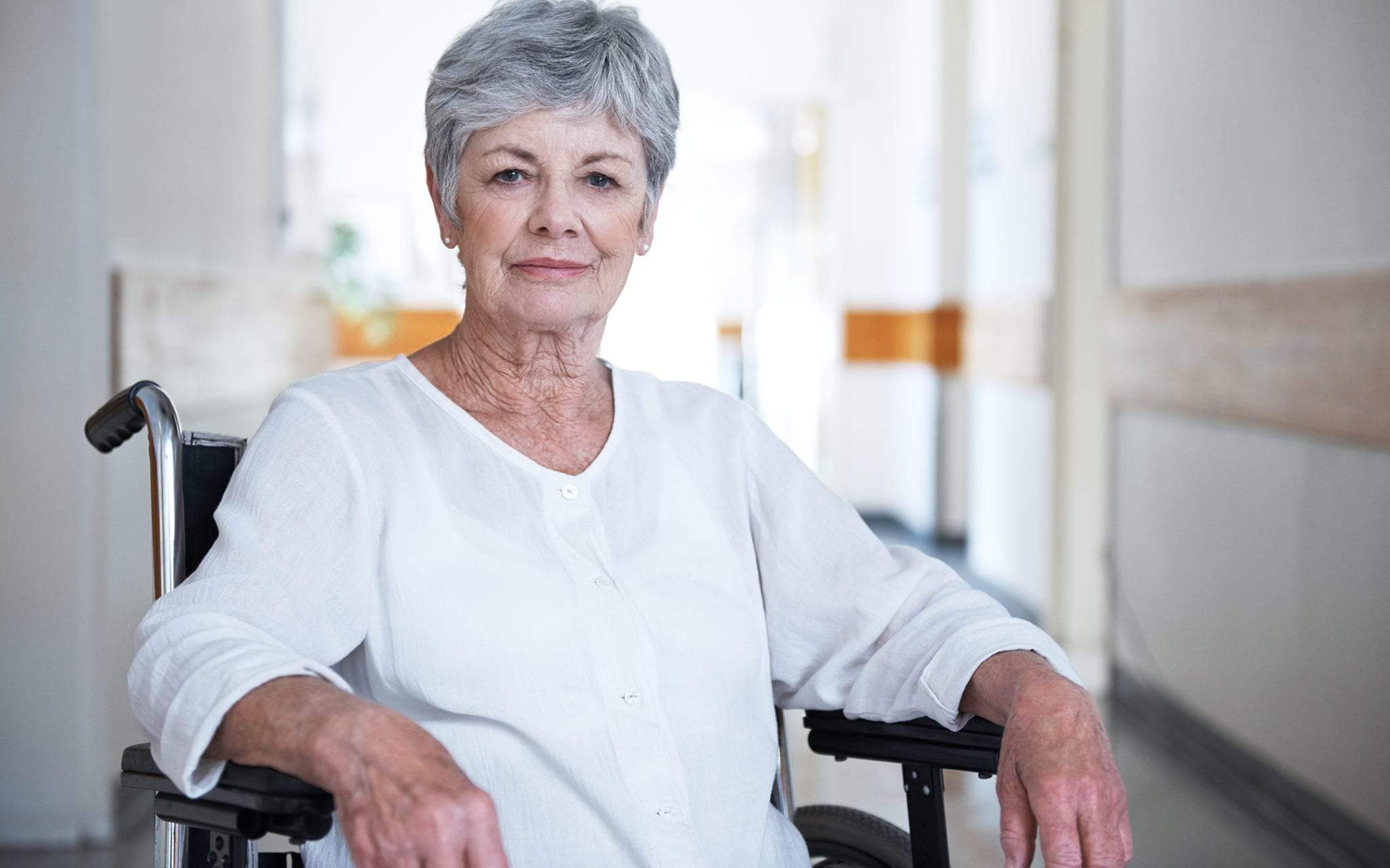 Medicare plan member, an older woman, sitting in wheelchair, at a doctor's office